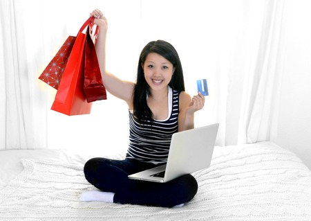 happy asian american woman online shopping at home photo