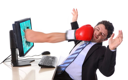 Business man with computer hit by boxing glove in stress and crisis concept photo