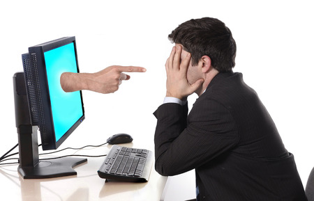 man in stress and crisis with computer finger pointing in social media cybermobbing and bullying