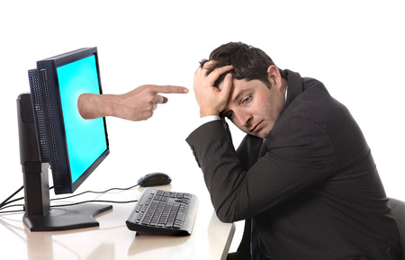 man in stress and crisis with computer finger pointing in social media cybermobbing and bullying  photo