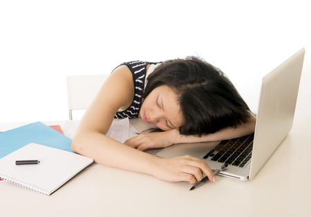 fatigued: young pretty chinese woman student asleep on her laptop from being overworked on a white background
