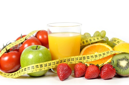 mix of fresh fruit , vegetables and orange juice in measure tape