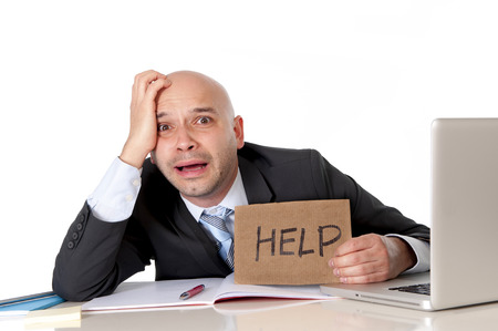 overworked unhappy bald business man in stress wearing suit holding help sign working on computer photo