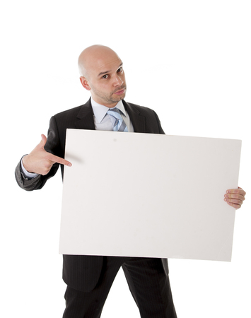 attractive bald business man wearing suit holding blank white advertisement sign on white background photo