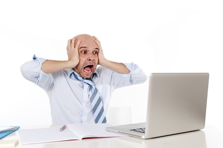 bald business man screaming in crisis at computer from pressure watching stocks crash  photo