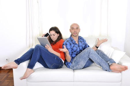 Latin couple sitting on couch boyfriend angry and girlfriend always busy with tablet and mobile phone photo