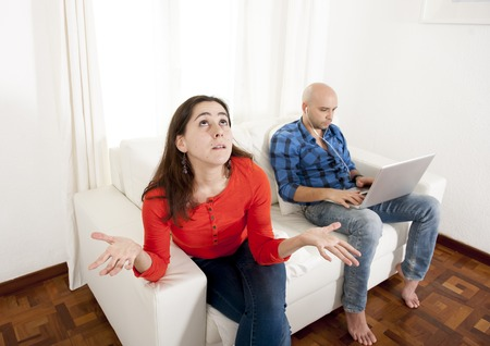 Latin couple sitting on couch with girlfriend angry and boyfriend always working or playing with tablet laptop at white living room.  photo