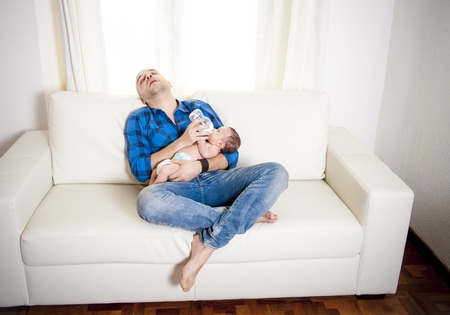 cradling: new bald latin father exhausted and asleep while feeding his newborn baby boy on a white couch in a white living room Stock Photo