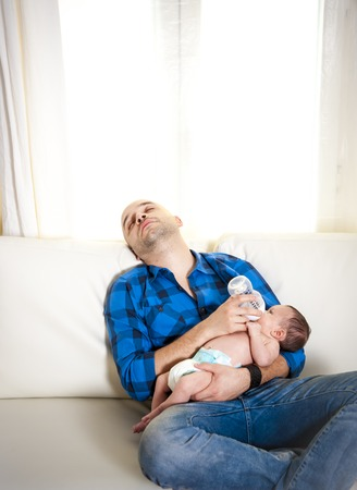 new bald latin father exhausted and asleep while feeding his newborn baby boy on a white couch in a white living room photo