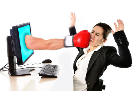 business woman with computer hit by boxing glove in social media cyber mobbing and bullying concept