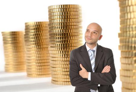 hombre calvo: Atractivo joven feliz del hombre de negocios con el pensamiento de la cabeza calva y so�ando con mucho dinero en pilas de monedas de oro de fondo
