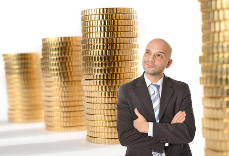 Attractive Happy Young Business Man with bald head Thinking and Dreaming of Big Money on gold coins stacks background