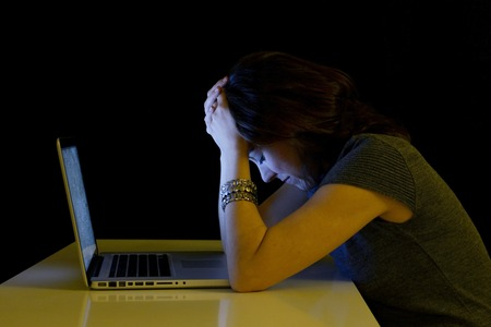 Jonge student vrouw alleen aan een bureau met computer huilen wanhopige lijden cyber pesten en pesten