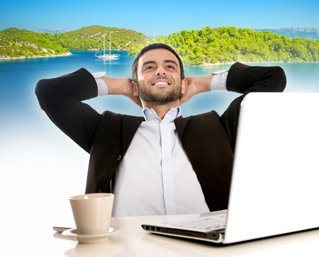 Business man with computer thinking and dreaming of summer vacation photo