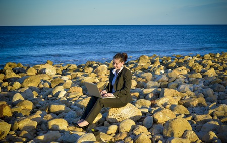 young beautiful business woman working on her laptop on the rocks at the beach  photo