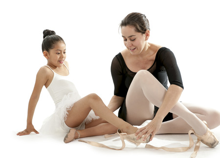 putting up: young pretty latin ballerina dance student and teacher putting on and tying up her dance shoes on a white background with copy space Stock Photo