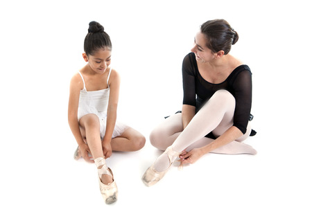 young pretty latin ballerina dance student and teacher putting on and tying up her dance shoes on a white background with copy space photo
