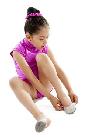 sit: young pretty latin ballerina dance student putting on and tying up her dance shoes on a white background