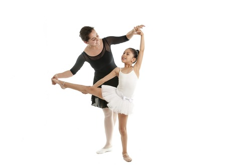 dance teacher: young beautiful ballerina being showing how to do a pose by her dance teacher on a white background