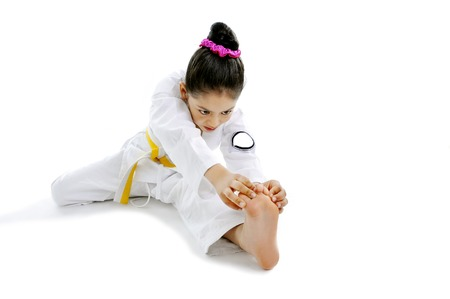 karate female: sweet latin little girl alone stretching leg in martial arts practice like karate kid  isolated on white background