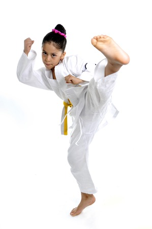 karateka: sweet latin little girl stretching leg in martial arts practice training kick and attack in plastic action like karate kid  isolated on white background