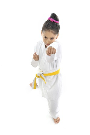 plasticity: sweet latin little girl training punch and attack in plastic action like karate kid isolated on white background Stock Photo