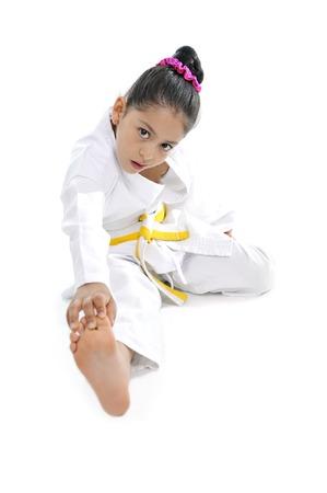 sweet latin little girl in kimono training and stretching leg like karate kid isolated on white background photo