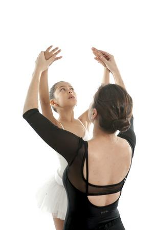 niños bailando: joven y hermosa bailarina está mostrando cómo hacer una pose por su profesor de baile sobre un fondo blanco Foto de archivo