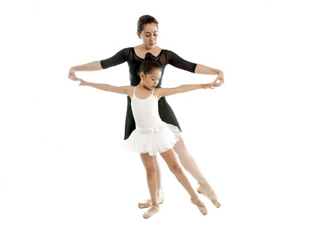 young beautiful ballerina being showing how to do a pose by her dance teacher on a white background