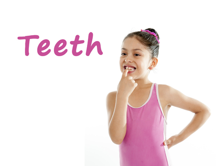 girl wearing a pink swimsuit pointing at her mouth and teeth on a white background for a school anatomy or body part chart Stock Photo