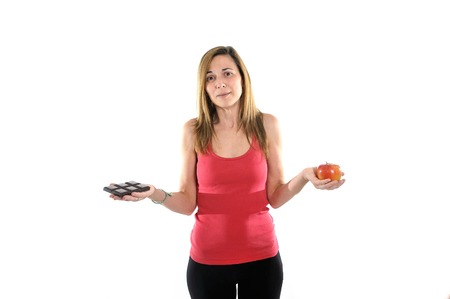 slim fit 40s Woman with Apple looking to Chocolate bar in health or temptation choice photo