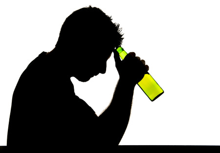 silhouette of alcoholic drunk young man drinking beer bottle feeling depressed falling into addiction problem Stock Photo