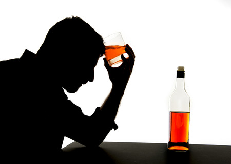 spirits: silhouette of alcoholic drunk man drinking whiskey bottle feeling depressed falling into addiction problem