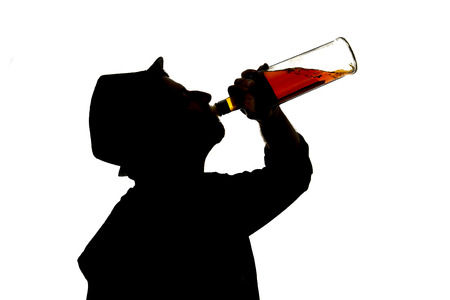 silhouette of alcoholic drunk young man with hat  drinking whiskey bottle feeling depressed falling into addiction problem photo