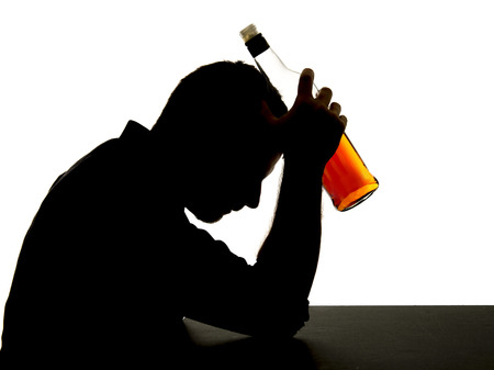 silhouette of alcoholic drunk man drinking whiskey bottle feeling depressed falling into addiction problem photo