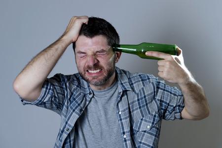 tomando alcohol: hombre loco que sostiene la botella de cerveza como una pistola con pistola apuntando a su cabeza en el alcoholismo y el suicidio metáfora aislado en gris Foto de archivo