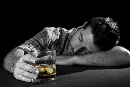 wasted: alcoholic wasted man sleeping drunk holding whiskey bottle and glass in alcohol addiction and alcoholism concept Stock Photo