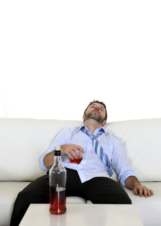 messy room: Attractive drunk business man lying asleep on couch at living room sleeping wasted holding whiskey glass in alcoholism problem , alcohol abuse and addiction concept looking messy and sick Stock Photo