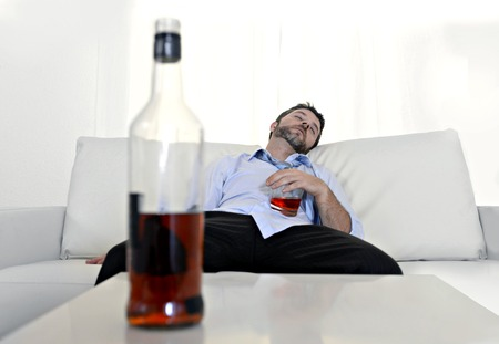 wasted:  drunk business man at home lying asleep on couch sleeping wasted holding whiskey glass in alcoholism problem , alcohol abuse and addiction concept looking messy and sick Stock Photo