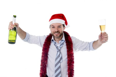 Happy attractive business man wearing santa hat with tinsel around neck in blue shirt and tie holding bottle and glass of champagne drinking at christmas party isolated on white