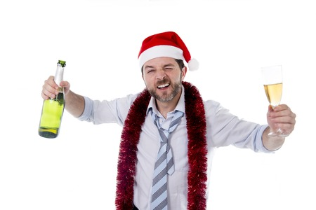 Happy attractive business man wearing santa hat with tinsel around neck in blue shirt and tie holding bottle and glass of champagne drinking at christmas party isolated on white  photo
