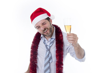 drunk happy attractive business man wearing santa hat with tinsel around neck in blue shirt and tie holding bottle and glass of champagne drinking at christmas party isolated on white