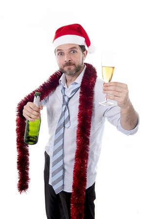 drunk happy attractive business man wearing santa hat with tinsel around neck in blue shirt and tie holding bottle and glass of champagne drinking at christmas party isolated on white  photo