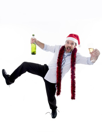 drunk happy attractive business man wearing santa hat with tinsel around neck in blue shirt and tie holding bottle and glass of champagne drinking and having fun at christmas party isolated on white
