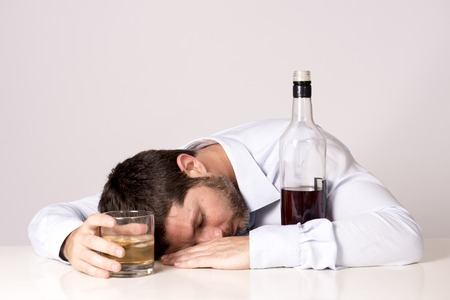 alcohol bottles: young attractive business man with beard  wearing blue shirt and tie drunk and drinking   Whisky sleeping on office desk at work isolated on clear