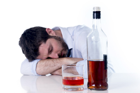 addictive drinking: young alcoholic business man with beard looking wasted suffering hangover wearing blue shirt and tie drunk and drinking  Whisky on office desk at work isolated on white  Stock Photo