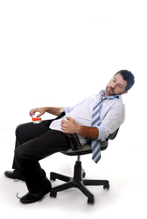 asleep chair: Attractive drunk business man sitting leaning back on office chair sleeping wasted holding whiskey bottle and glass in alcoholism problem , alcohol abuse  concept isolated on white vertical composition
