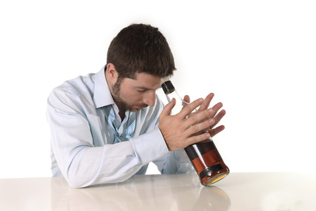 Attractive drunk business man lying on desk wasted and holding whiskey bottle against forehead  in alcoholism problem , alcohol abuse and addiction  isolated on white  photo