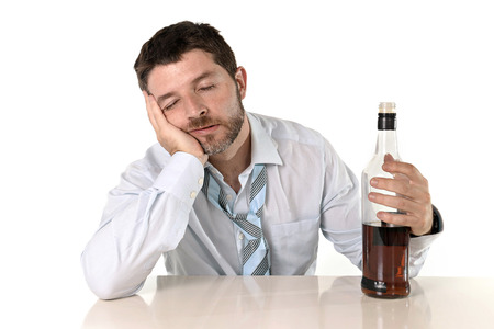 wasted: Attractive drunk business man lying on desk wasted and holding whiskey bottle in alcoholism problem , alcohol abuse and addiction concept isolated on white  Stock Photo