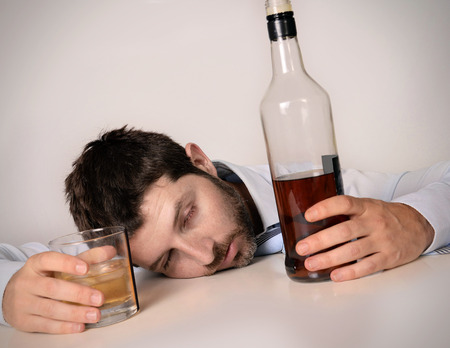 wasted:  drunk business man lying on desk wasted and holding whiskey bottle and glass in alcoholism problem , alcohol abuse and addiction concept isolated on grey